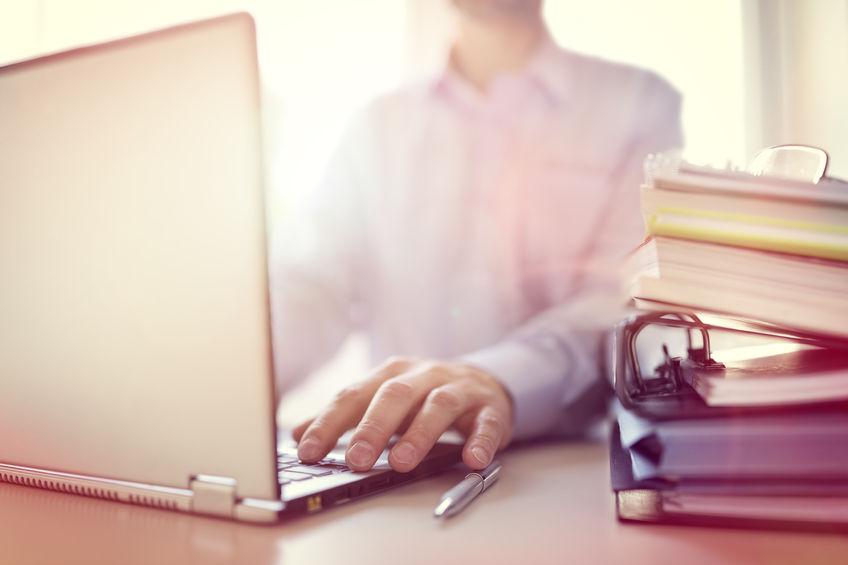 54427913 - businessman or designer using laptop computer at desk in office