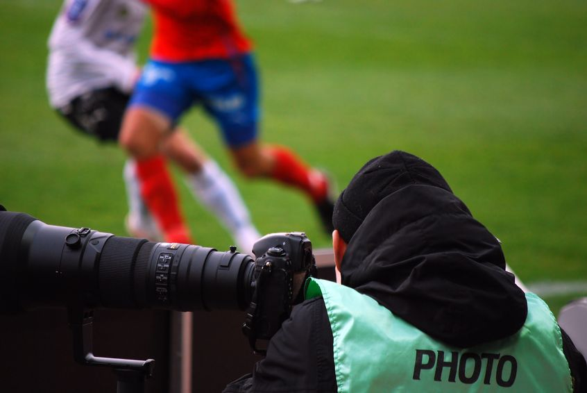 7090980 - a sports photographer watches and shoots the action at a football match.
